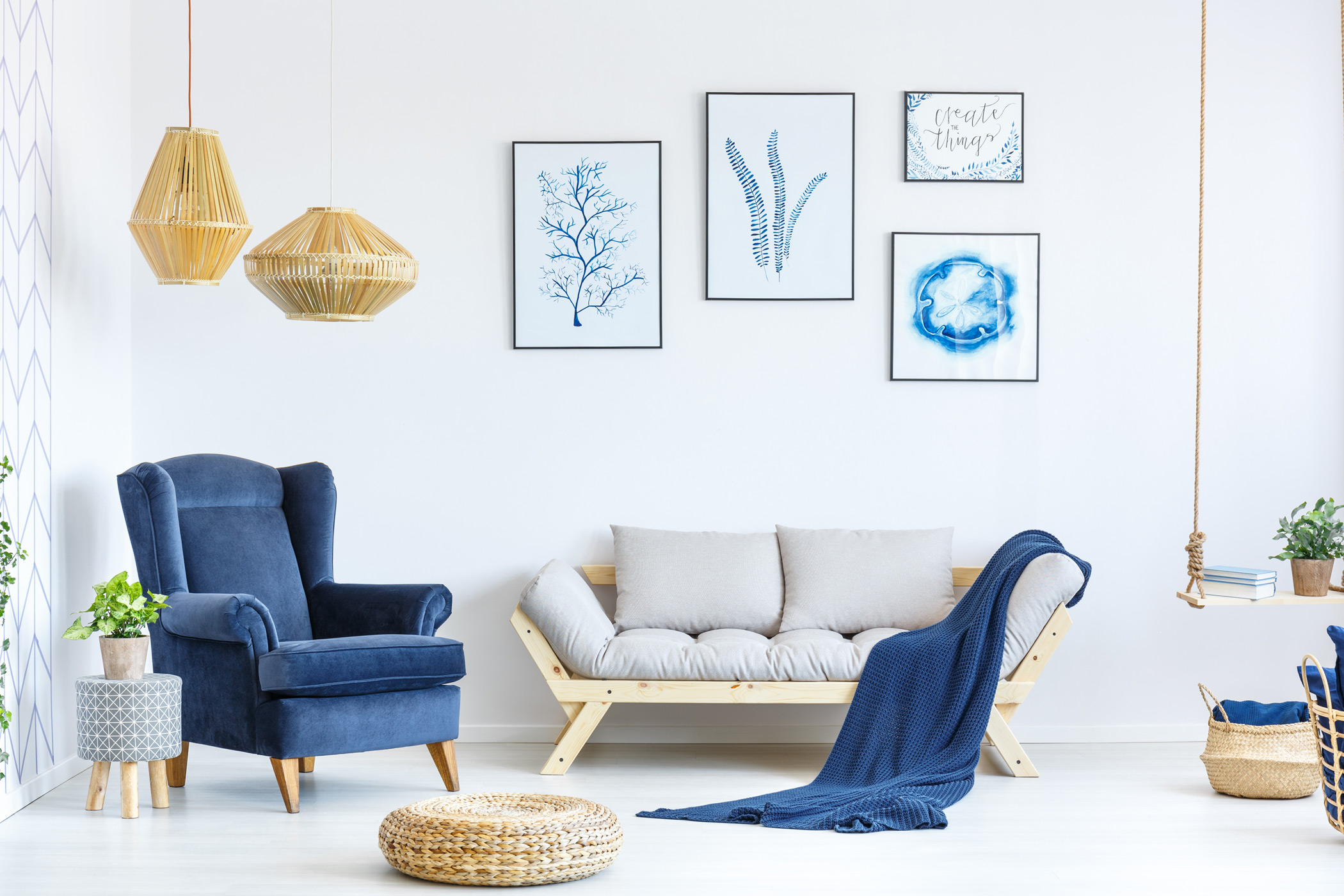 a beautifully decorated living space with three hanging wall art in frames, a velvet couch and with throw pillows and a blanket