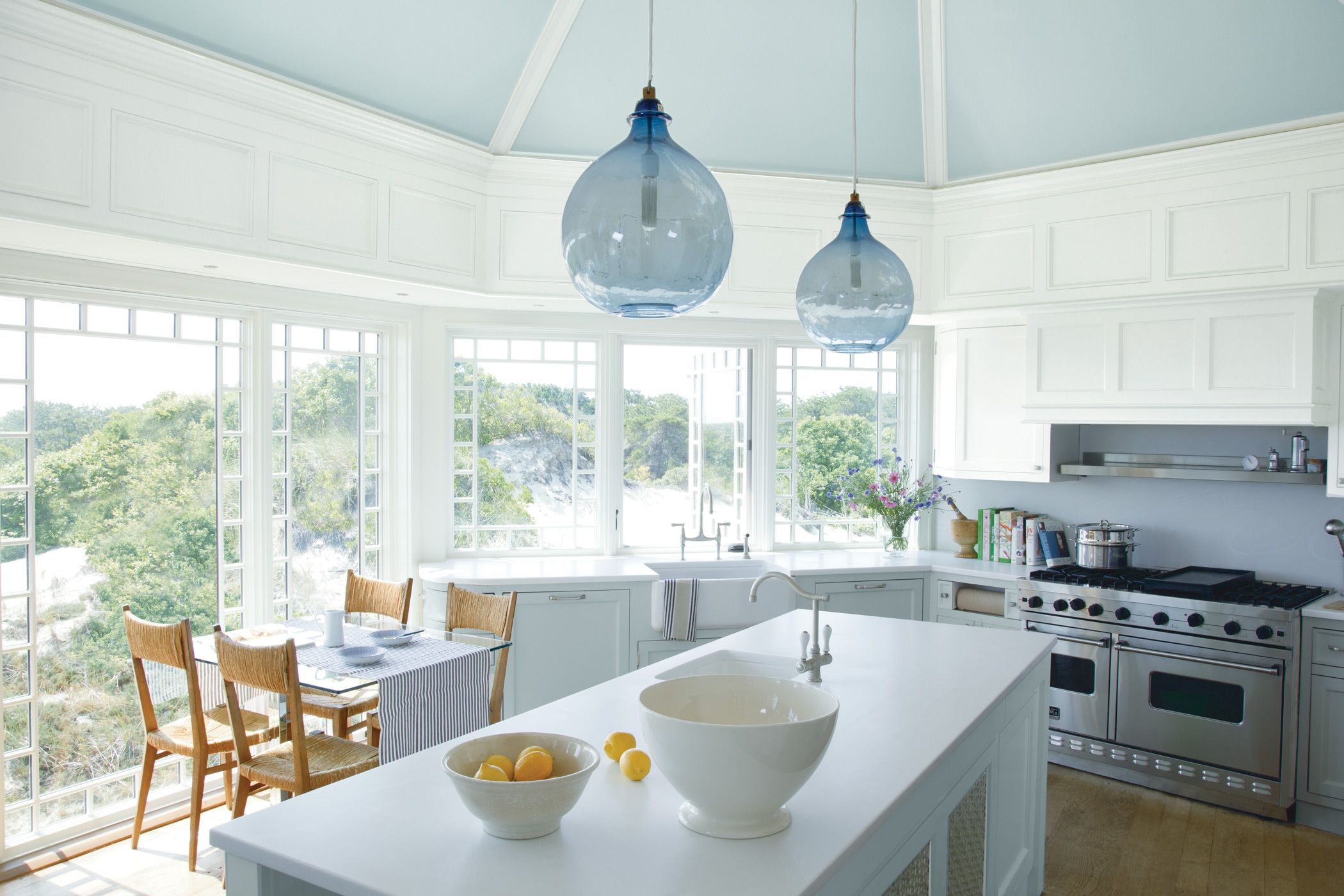 a bright and cheery kitchen with white walls and cabinets surrounding an island under big glass hanging lights