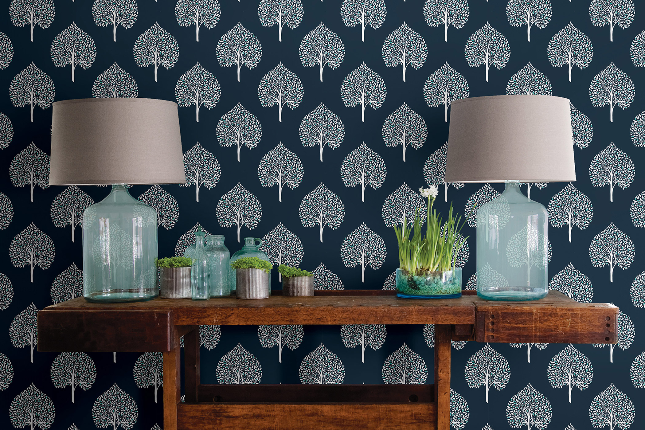 a wooden table displaying two glass table lights and simple plants in front of big impressive wallpaper