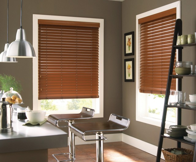 an office room decorated neatly with deep wooden blinds covering large windows