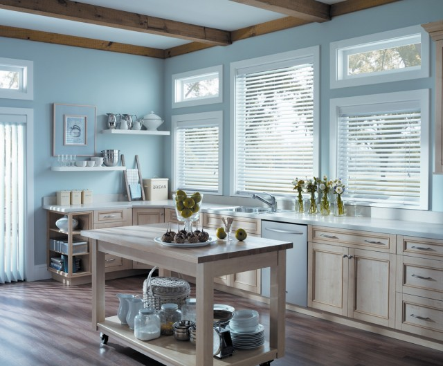 a bright blue kitchen with light cabinets with white blinds opened to the sunny day