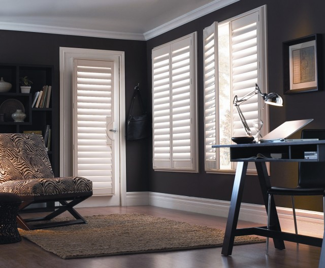 a deep lounge room with a desk and chair and windows covered with clean white shutters opened to the day