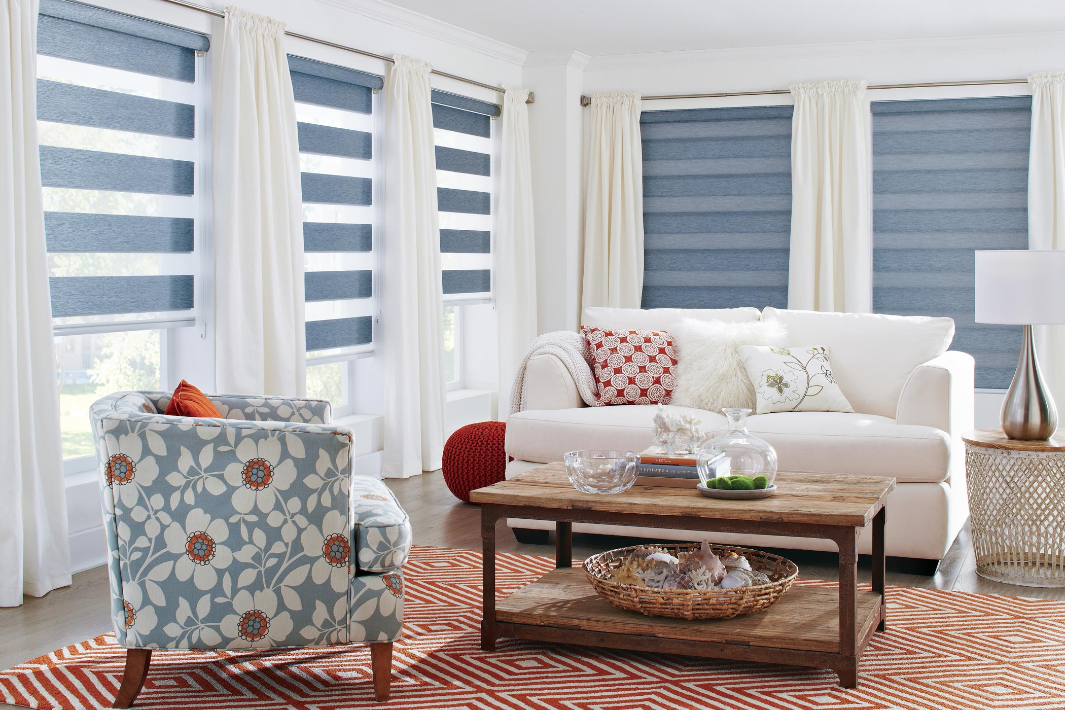 a bright white living room with a floral print chair and throw pillows with windows covered in striped dual shades