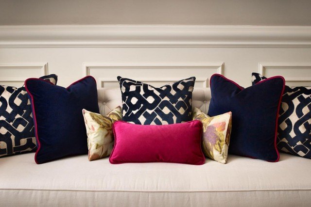 a bench with a ton of different patterned throw pillows