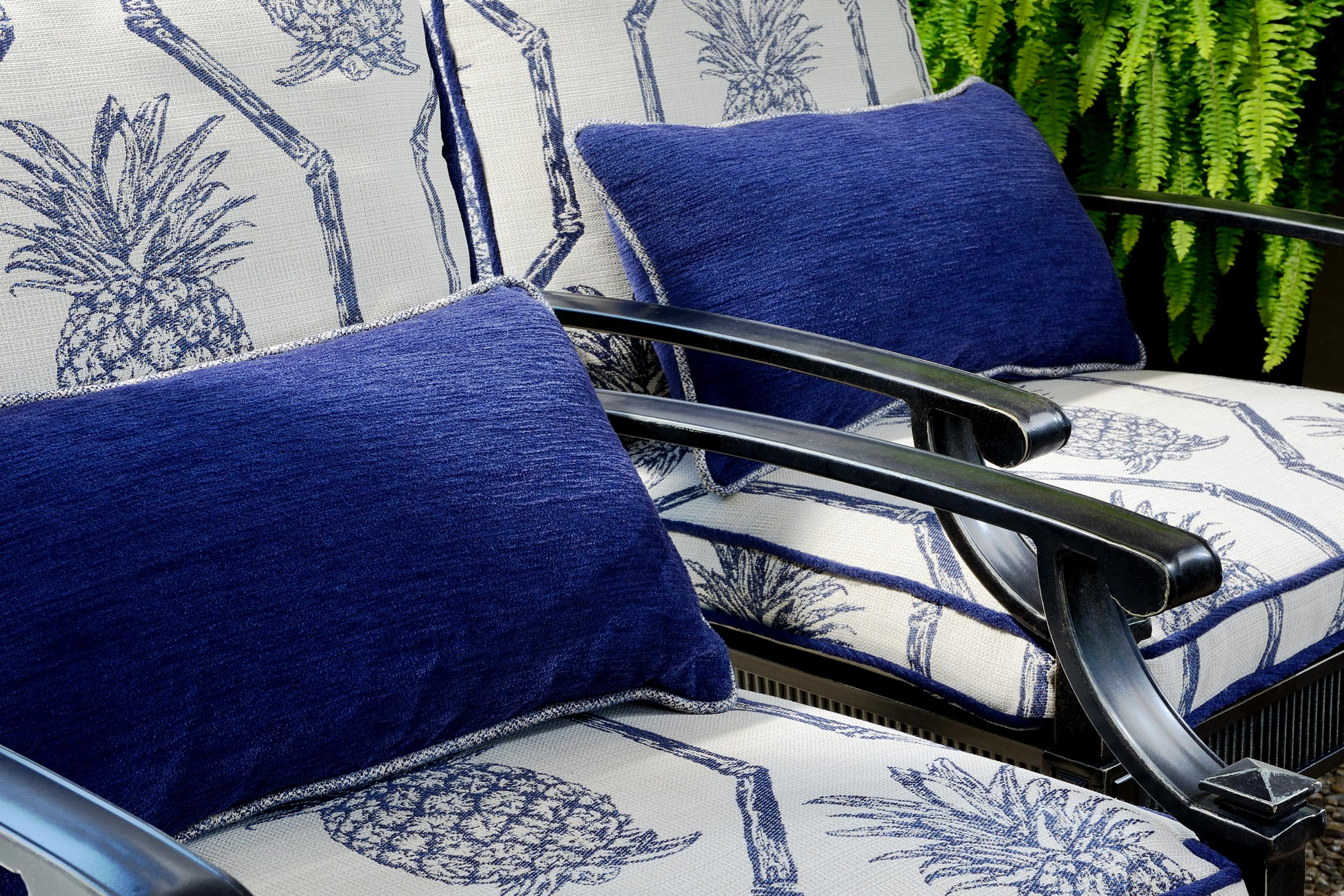 two outdoor lounge chairs covered with beautiful pineapple upholstery and deep blue pillows