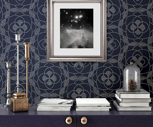 a display table decorated with candles and books infront of artwork and deep patterned wallpaper