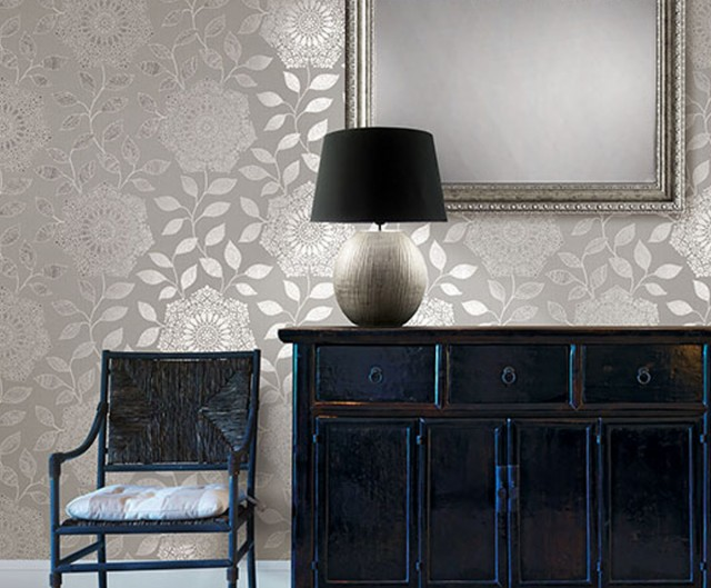 a table holding a small table lamp next to a wooden chair under a large mirror and a leaf patterned glossy wallpaper